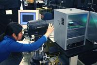 Photo: LRC graduate student Hua Yu examines a quantum-dot LED.