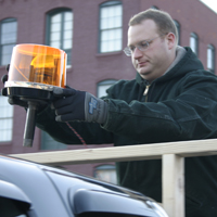 Nick Skinner adjusts an LED beacon on top of a car